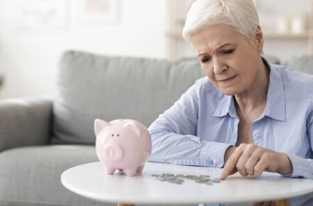 Upset elderly woman counting last coins from piggy bank, sitting depressed at home