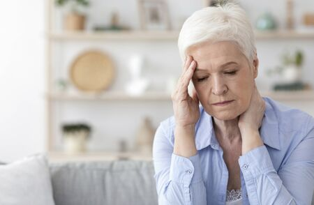 Senior Woman Suffering From Headache At Home, Sitting On Couch Touching Temple, Feeling Unwell