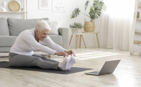 Home Sport. Active Senior Woman Doing Warming Stretching Exercises In Front Of Laptop, Training With Online Tutorials Stock Photo