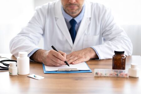 Close up of medical practitioner filling in paperwork sitting at desk in his in office
