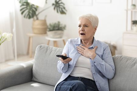 Coronavirus News. Shocked Senior Woman Watching Tv At Home, Holding Remote Controller, Sitting On Cozy Couch Stock Photo