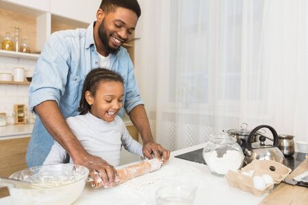 Smiling Black Man And His Daughter Rolling Dough Together At Kitchen, copy space