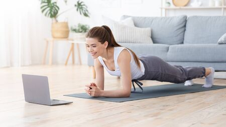 Positive girl planking at home, using laptop, morning exercise concept, panorama with copy space