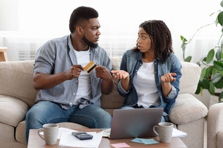 Budget Fail. Angry Black Husband Scolding His Wife For Spending Over Credit Limit While They Sitting Together On Couch At Home, Free Space