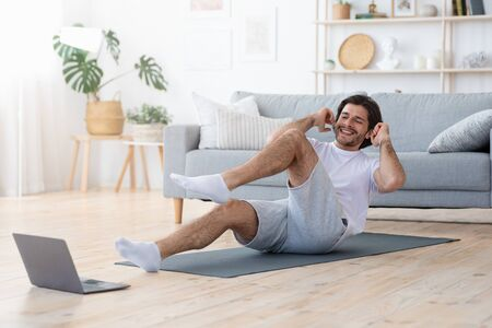 Fitness channels online. Positive guy making exercises at home, looking at laptop screen, copy space