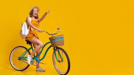 Summer Sale. Excited Young Girl Riding Vintage Bicycle And Pointing Aside At Copy Space Over Yellow Background Standard-Bild