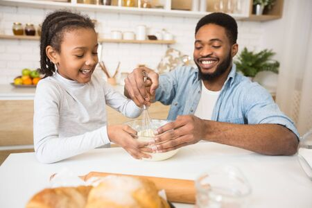 Cheerful African Dad Teaching His Lovely Daughter How To Mix Dough At Home Kitchen 写真素材