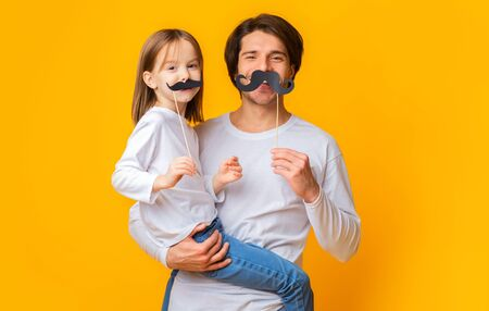 Portrait of cheerful father and daughter having fun over yellow studio background, puting mustaches on sticks