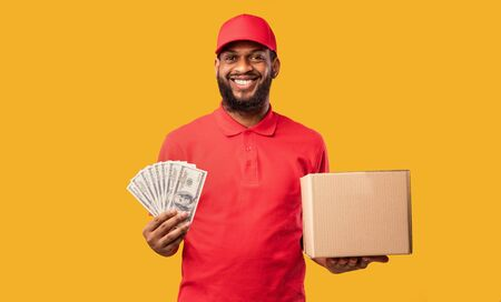 Pay On Delivery. African Courier Guy Holding Money Cash And Cardboard Box Standing On Yellow Background. Studio Shot