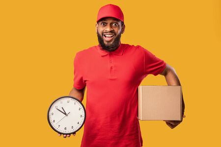 Express Delivery. Joyful Courier Holding Cardboard Box And Clock Delivering In Time Standing Over Yellow Background. Studio Shot Standard-Bild