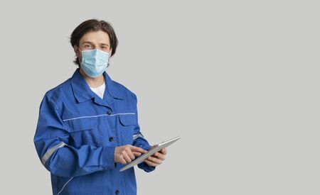 Young Quantity Surveyor Wearing Medical Mask And Using Digital Tablet, Working During Coronavirus Global Pandemic, Light Background With Free Space