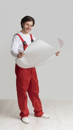 Repairment Plan. Smiling Young Engineer Holding Blueprint, Checking Project Details, Standing Over Light Studio Background