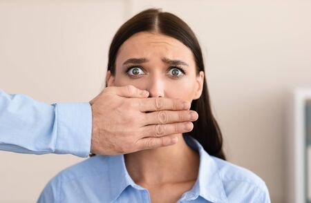 Sexual Harassment At Work. Boss Harassing Scared Employee Girl, Covering Mouth With Hand Making Her Keep Silence In Office.