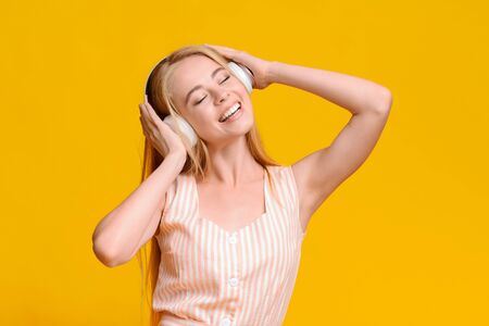 Favorite Leisure. Cheerful Teen Girl In Wireless Headphones Listening Music, Enjoying Songs With Closed Eyes, Standing On Yellow Background, Free Space