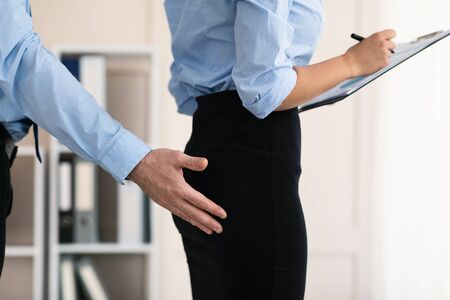Sexual Harassment At Work. Boss Touching Employee Womans Butt Harassing Her Sexually At Workplace In Modern Office. Cropped