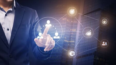 E-business management concept. Businessman touching icon with human on e-business process hologram over skyscraper, panorama