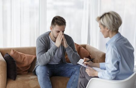 Depression Counseling. Desperate Man Telling About Unhappy Life While Professional Psychologist Taking Notes During Appointment In Office. Selective Focus