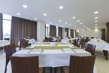 Tables and chairs in large restaurant hall. Empty room, ready for dinner