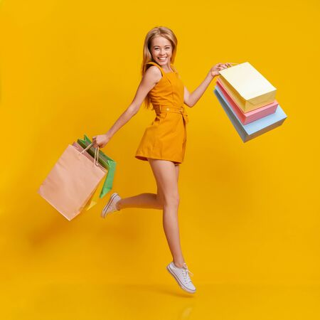 Seasonal Sales. Beautiful Shopaholic Young Girl Jumping In Air With Lots Of Shopping Bags In Hands Over Yellow Studio Background, Free Space