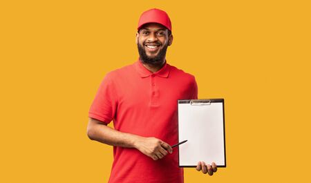 Parcel Receiving. Delivery Man Holding Folder With Blank Paper Delivering Goods Standing Over Yellow Studio Background. Mockup 版權商用圖片 - 146712484
