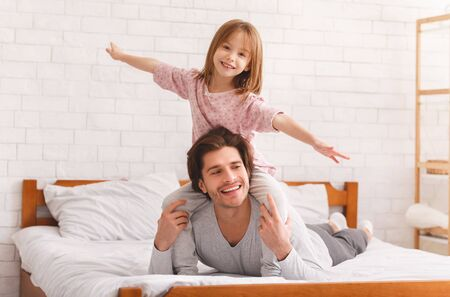 Positive little girl sitting on father shoulders, imitating airplane, dad laying on bed, free space