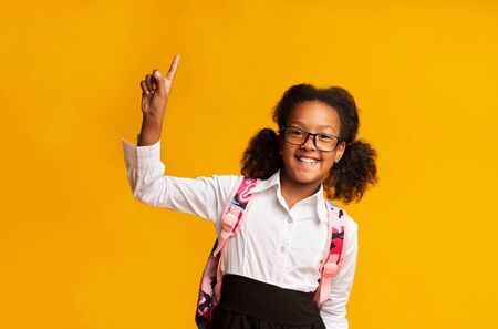 Smiling Schoolgirl Pointing Finger Up Having Question About Home School Learning During Quarantine Posing Over Yellow Background. Stock Photo