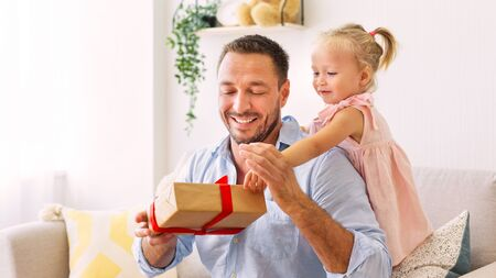 Celebration Concept. Charming little girl congratulating father and giving gift box to him, copy space