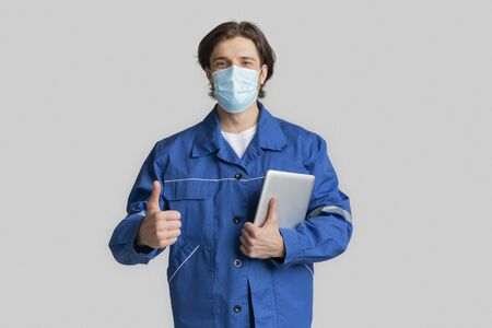 Coronavirus Protection At Work Sites. Portrait Of Civil Ingineer Wearing Medical Mask Holding Digital Tablet And Showing Thumb Up Gesture, Copy Space Archivio Fotografico