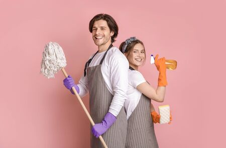Professional Cleaning Service. Portrait Of Smiling Man And Woman With Household Tools In Hands Standing Back To Back Over Pink Studio Background