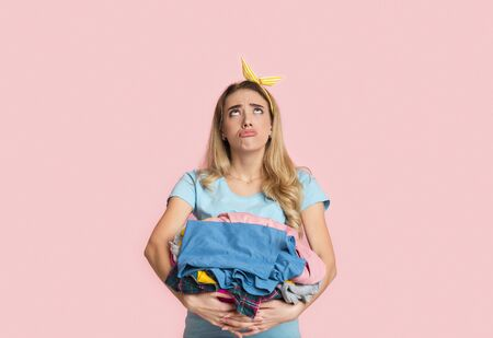 Routine household chores concept. Sad housewife blowing lips, looks up and holds clothes