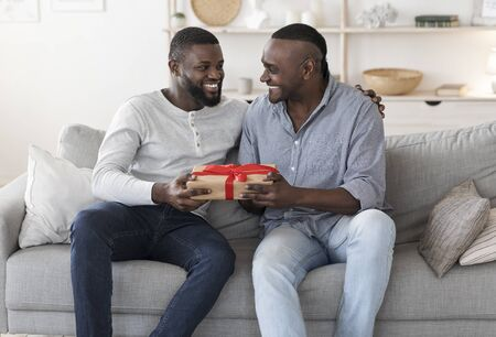 Happy Fathers Day. Adult Black Son Congratulating His Senior Dad, Surprising Him With Gift, Giving Present While Sitting On Couch At Home Stock fotó
