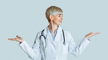 Medicine specialist. Woman in white coat chooses different options, weighing on her hands, isolated on light background, studio shot