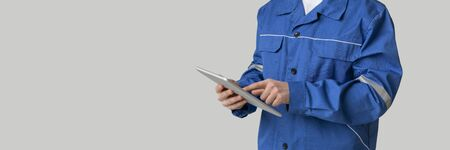Application For Construction. Digital Tablet In Hands Of Unrecognizable Laborer In Work Uniform, Cropped Image, Panorama With Copy Space Archivio Fotografico