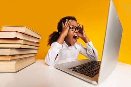 Distant Online Education. Overworked Schoolgirl Shouting At Laptop Tired Of Quarantine Homework Sitting At Desk On Yellow Studio Background