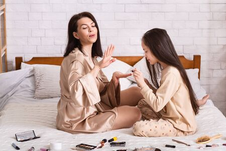 Beauty salon at home. Mom and daughter doing each others nails in bedroom
