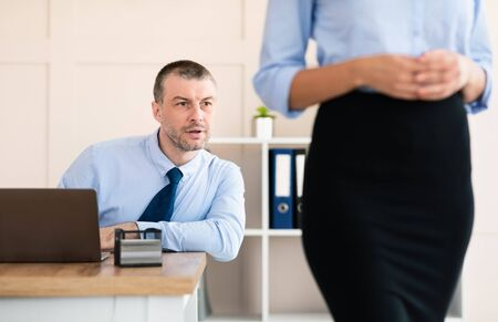 Sexual Harassment. Lustful Businessman Staring At Colleague Womans Butt Sitting At Workplace In Modern Office. Selective Focus Imagens