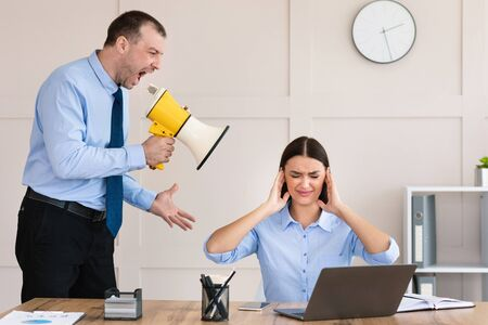 Aggressive Businessman Shouting At Employee Woman Holding Megaphone Standing In Modern Office. Professional Comunication Problem Foto de archivo
