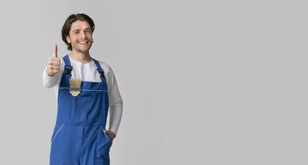Repair And Renovation. Smiling handyman with paintbrush in pocket showing thumb up, posing over light background in studio, panorama with copy space Фото со стока
