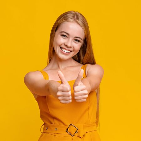 Joyful Teen Girl Gesturing Thumbs Up At Camera Isolated Over Yellow Background, Closeup Portrait Фото со стока