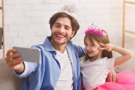 Happy father and daughter wearing as princesses taking selfie at home, happy moments together