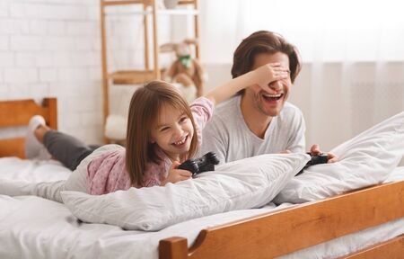 Playful kid girl covering her dad eyes while playing videogame, cheating to win, free space