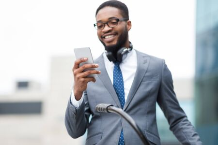 Business Chat. Smiling black businessman in glasses using cellphone, holding bicycle outdoors, copyspace