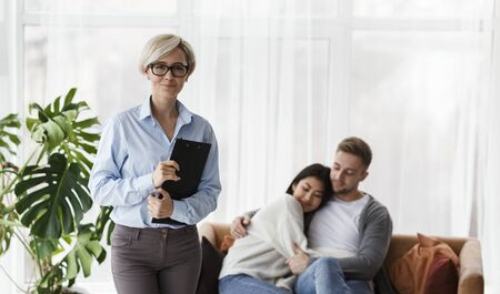 Successful Psychotherapy Session. Family Counselor Standing Smiling To Camera After Couples Reconciliation In Office. Selective Focus