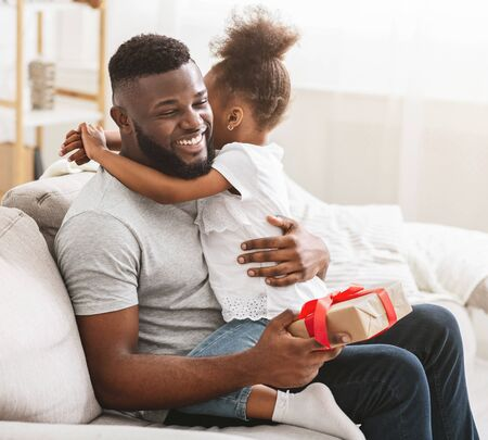 International Fathers Day concept. Thankful black man holding gift and hugging his little daughter, home interior 스톡 콘텐츠