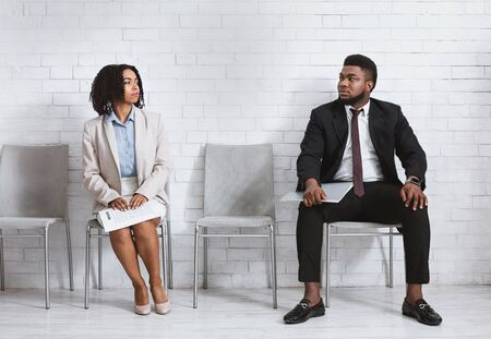 Male and female vacancy candidates looking at each other with antipathy while waiting for job interview in office lobby