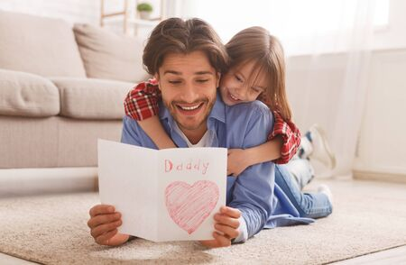 Emotional father reading greeting self-made card while bonding with daughter on floor at home, free space