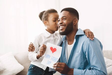 Happy Fathers Day. Cute Daughter Kissing Dad In Cheek And Giving Handmade Card