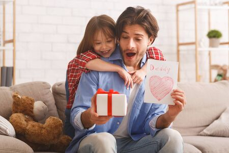 Happy Father Day, adorable girl greeting her daddy with gift and self-made card, dad is happy, copy space