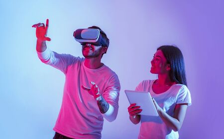 Couple with gadgets. Guy in virtual reality glasses and hands up, smiling girl looks at him and holds tablet, in neon, studio shot