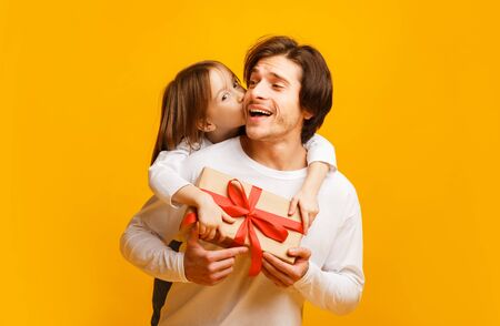 Adorable little daughter and father holding gift box, girl kissing dad from behind, Father Day concept, yellow background